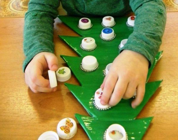 Ребёнок выкладывает крышечки от пластиковых бутылок на шаблоне ёлочки