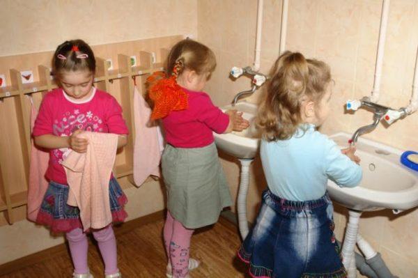 Три девочки моют и вытирают руки