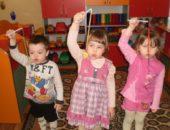 Трое детей дуют на подвешенные на лентах фигурки