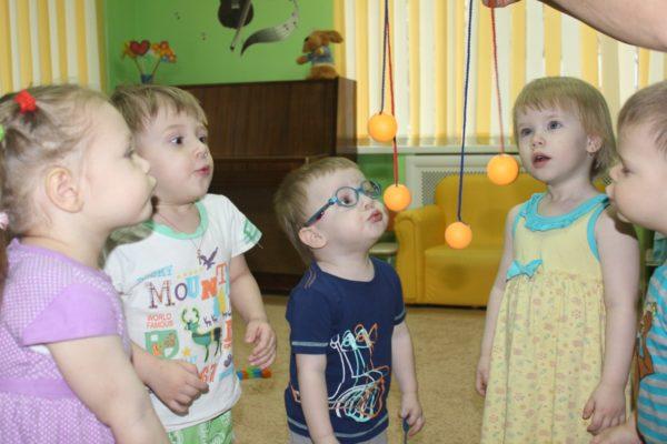 Воспитанники младшей группы дуют на подвешенные шарики