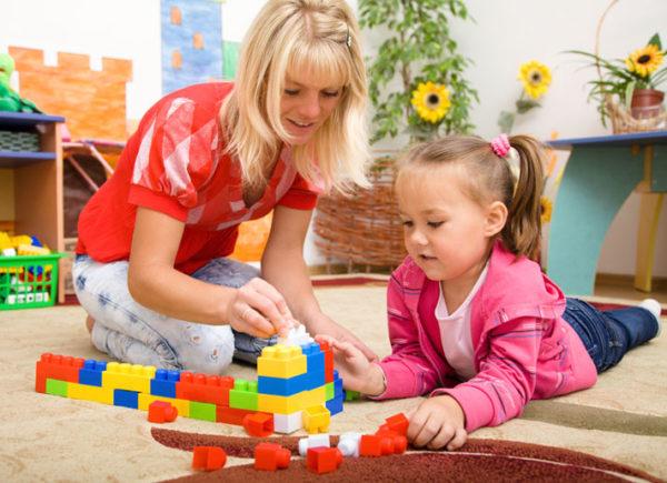 воспитатель и ребенок строят дом