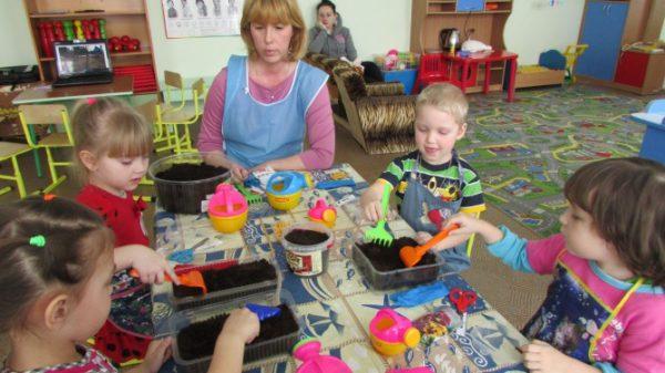 Воспитатель с детьми рыхлят землю в контейнерах