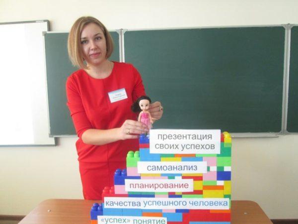 Воспитатель с макетом составляющих успешного педагога