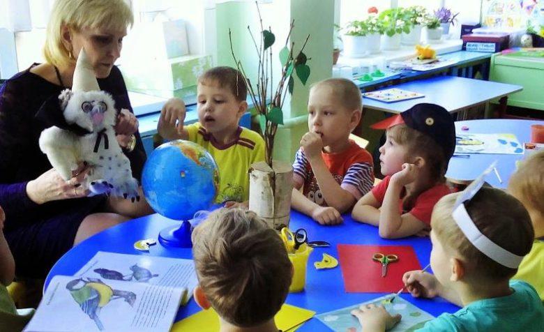 Воспитательница с игрушкой в руках беседует с детьми