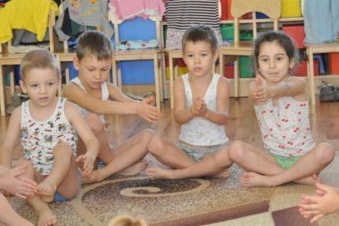 Четверо детей выполняют упражнение, сидя на полу