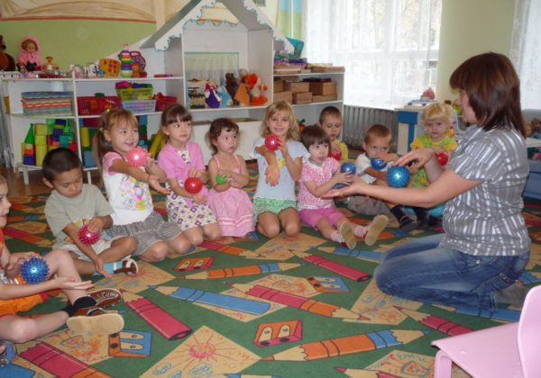 Дети и педагог делают себе массаж массажными мячиками
