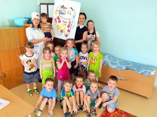 Дети и педагог держат большой рисунок зуба