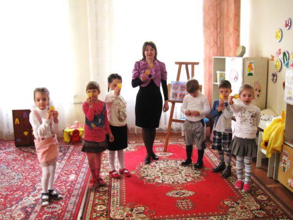 Дети и педагог держат в руках жёлтые смайлики