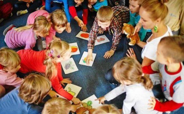 Дети и педагог играют с картинками, на которых изображены фрукты