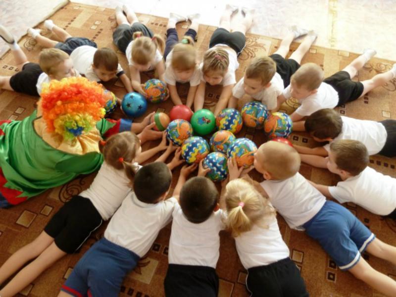 Дети и педагог в костюме клоуна с мячиками лежат на полу