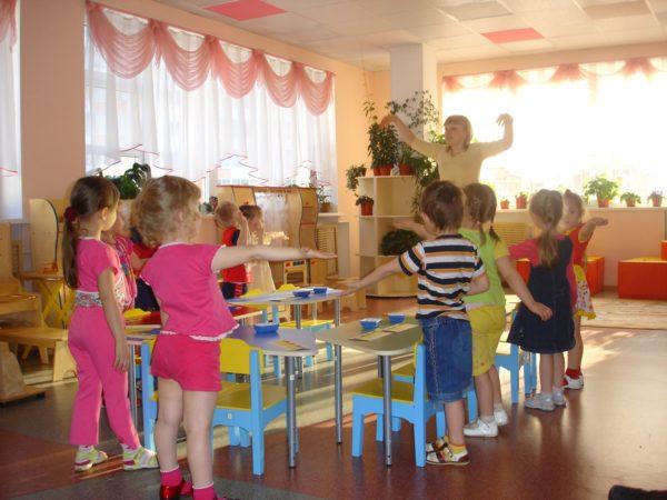 Дети и педагог выполняют упражнение физкультминутки