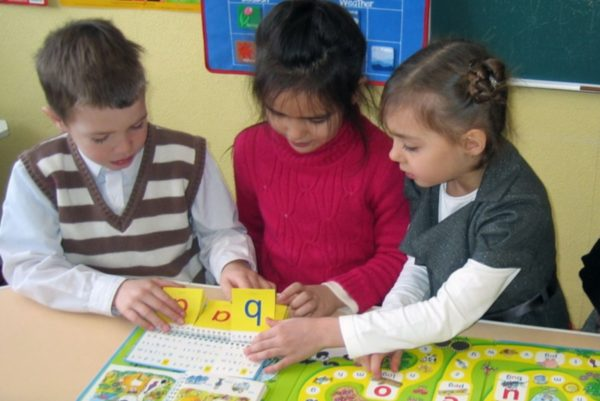 Дети играют с карточками с английским алфавитом