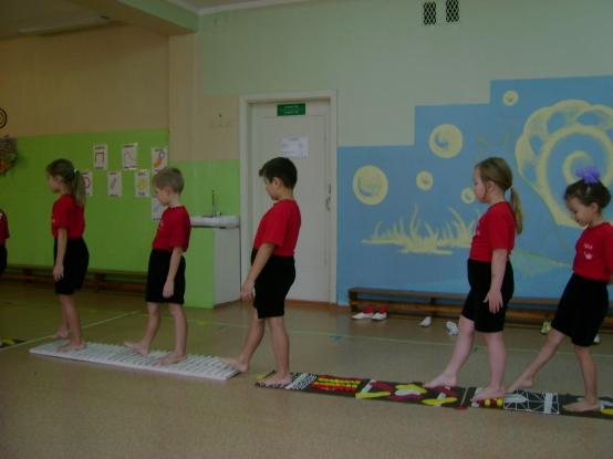 Дети на физкультуре идут по массажным коврикам