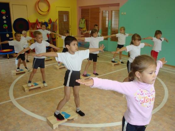 Дети выполняют упражнение на физкультуре