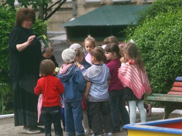 Дети на улице стоят вокруг воспитательницы
