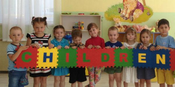 Дети с большими пазлами в руках со словом «children»