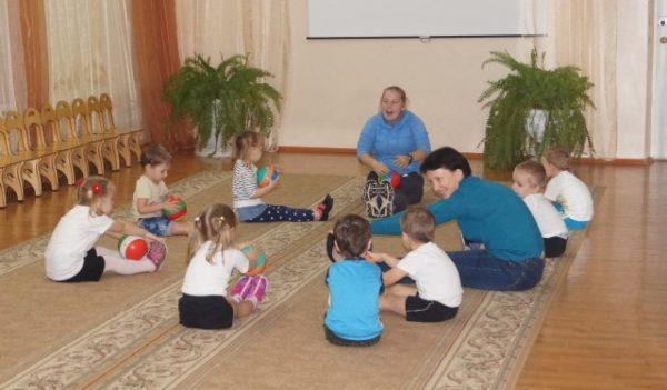 Дети с двумя воспитателями сидят на коврике
