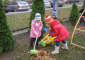 Дети сгребают осенние листья на участке