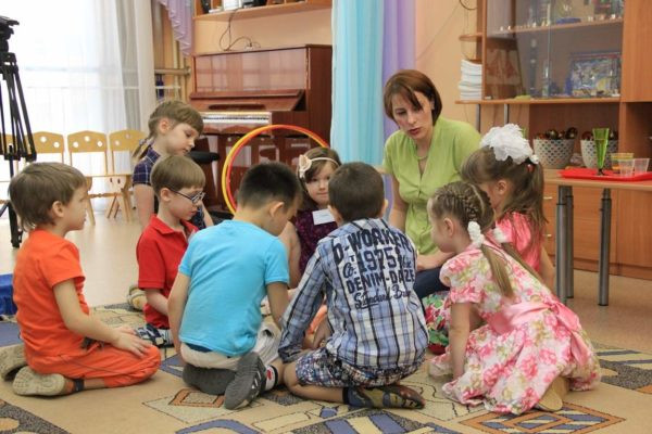 Дети и педагог сидят на ковре в кругу