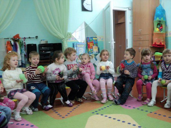 Дети сидят в кругу с мячиками в руках