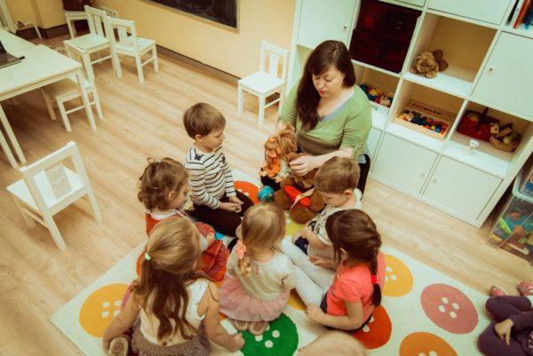 Дети сидят вокруг педагога, держащего в руках куклу