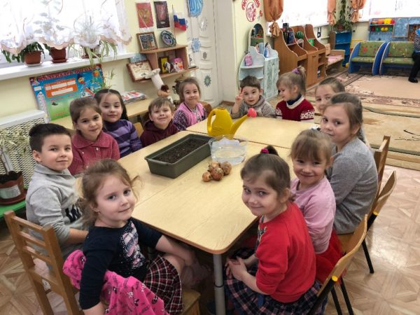 Дети сидят за столом, на котором находится контейнер с землёй