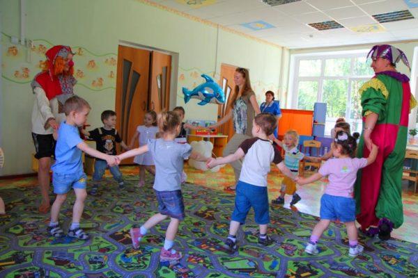 Дети со взрослыми в костюмах водят хоровод