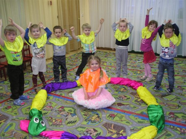 Дети стоят с поднятыми руками вокруг девочки в оранжевой пелерине