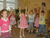 Дети стоят с поднятыми вверх руками