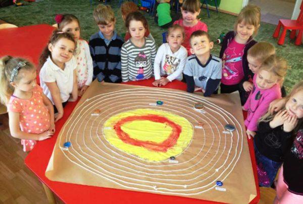 Дети стоят вокруг макета Солнечной системы