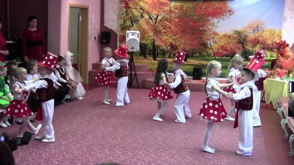 Дети танцуют в костюмах мухоморов