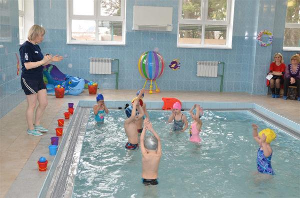 Дети выполняют упражнение в бассейне