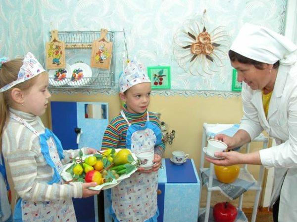 Дети в фартуках держат тарелку с муляжами фруктов