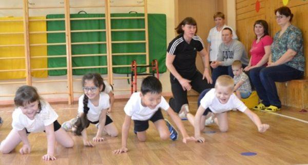Дети выполняют физическое упражнение в спортивном зале