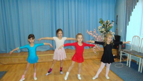 Четыре девочки выполняют танцевальное движение