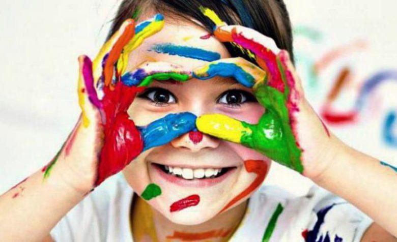 Девочка приложила к лицу руки в красках