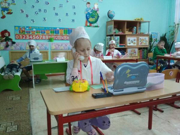 Девочка в костюме врача сидит перед маленьким нетбуком