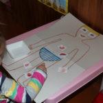 Девочка выкладывает на рисунок тела человека картинки частей тела и органов