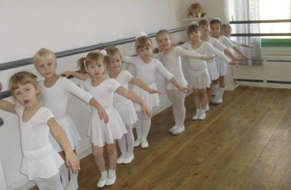 Девочки стоят у балетного станка
