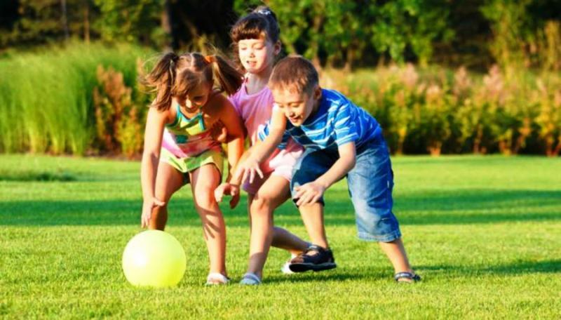 Две девочки и мальчик играют на лужайке в мяч