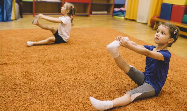 Две девочки тянут ножки на ковре
