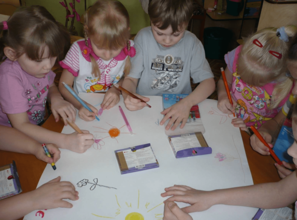 Дети делают совметный рисунок на листе ватмана