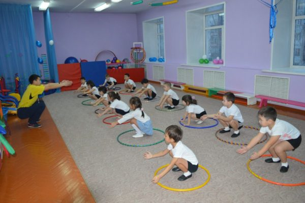 Инструктор по физкультуре показывает детям упражнение в обруче