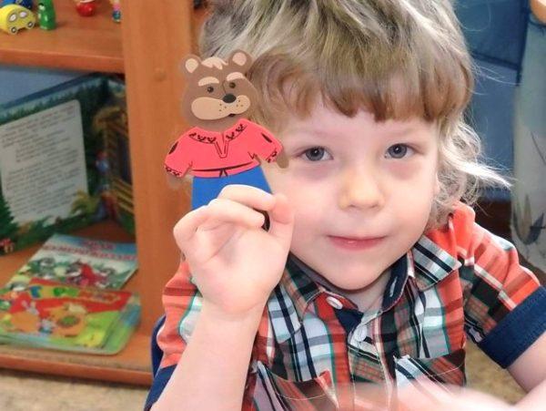 Мальчик держит фигурку картонного медведя