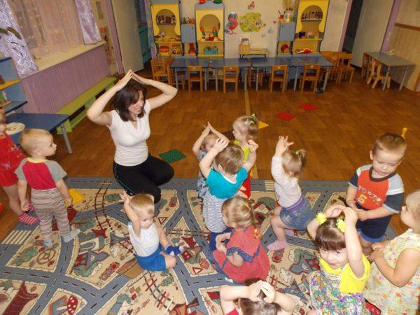 Педагог и дети на коврике сложили ручки домиком над головой