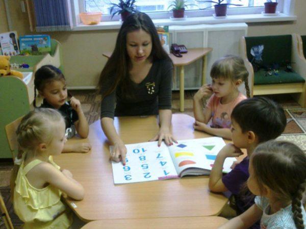 Дети и педагог работают с пособием с цифрами и формами