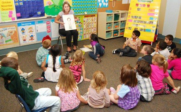 Педагог показывает картинку детям, сидящим на коврике
