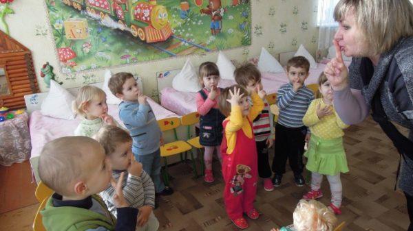 Педагог показывает малышам жест тише
