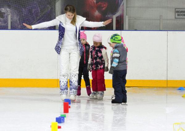 Тренер показывает детям как на коньках объезжать кубики
