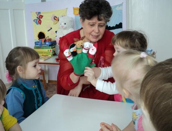 Воспитатель показывает детям кукол на перчатке